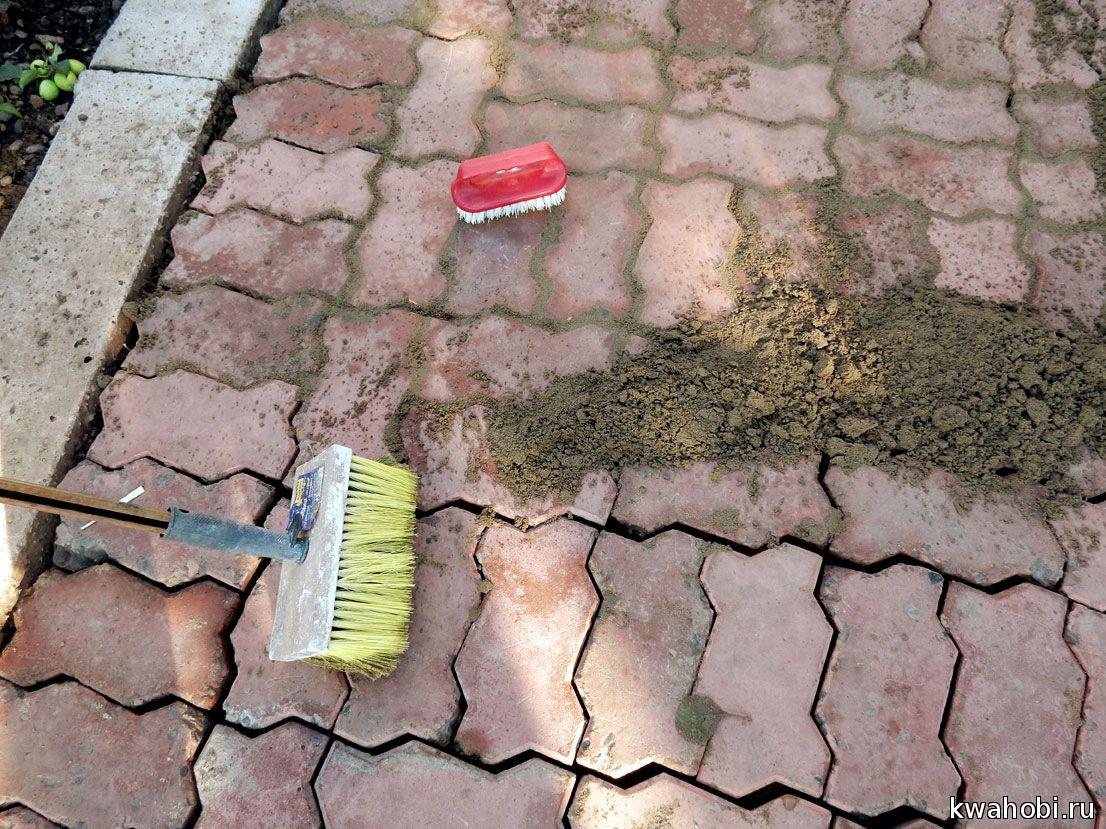 песок втирается между бордюрными камнями жесткими щётками. Сначало нужно использовать большую щётку на палке