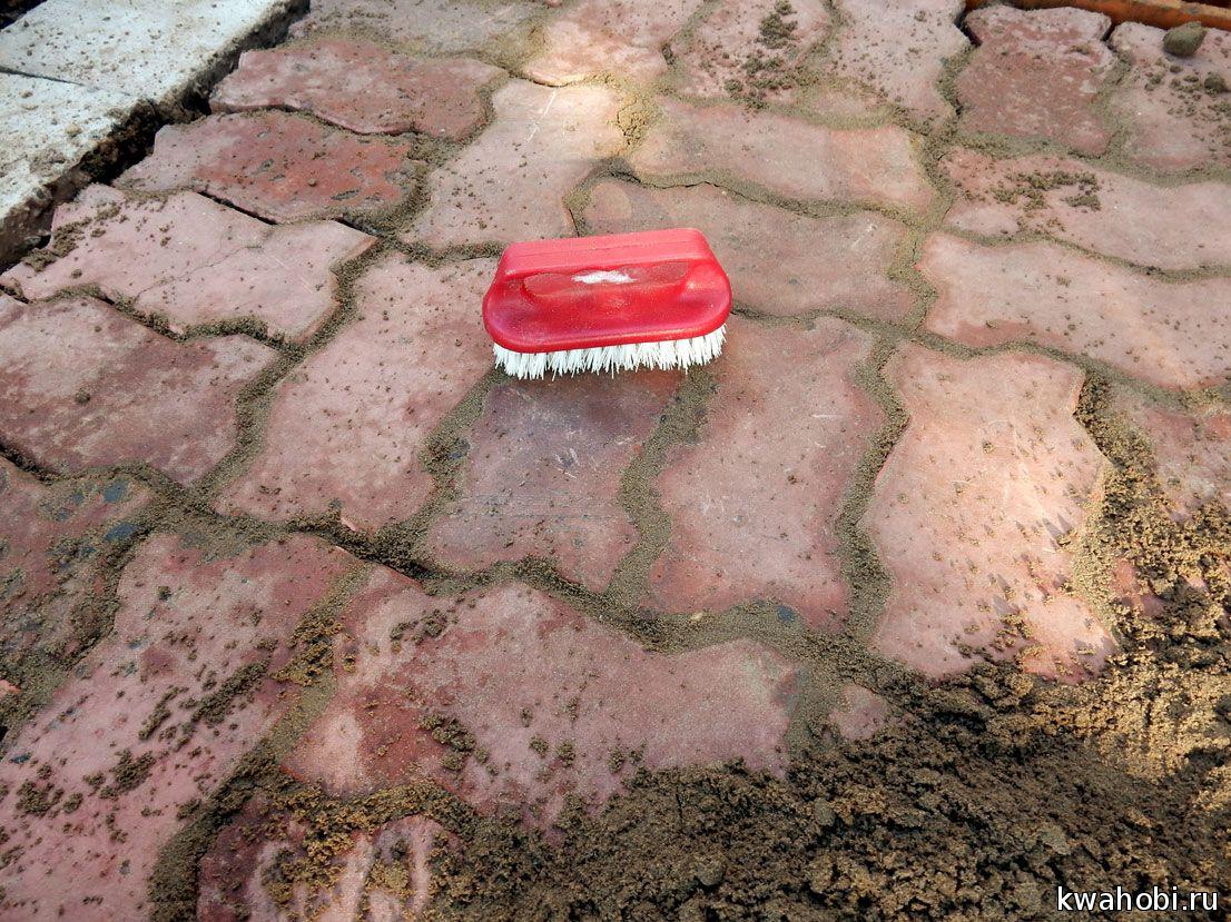 дотирается песок ручной жесткой щёткой. На фото видно, что песок мокрый, что не есть хорошо.